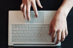 Wooden desktop top view, male hands typing on the laptop keyboard royalty free stock images