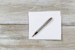 Wooden Desktop with white envelope and pen Royalty Free Stock Images