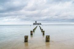 Wooden destroyed breakwaters line and ruins of torpedownia on Baltic Sea. stock images