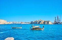 Dghajsa water taxi in Valletta, Malta. The wooden dghajsa boats are traditional Maltese water taxi, offering trips from Valletta ferry port around Grand Harbour Royalty Free Stock Images
