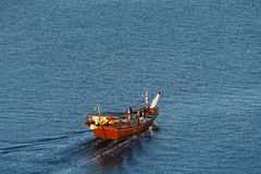 A wooden Dhow Sails into the Dubai Creek at dawn Royalty Free Stock Image