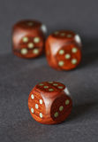 Wooden dice. Three wooden dice on a grey neutral background Royalty Free Stock Photos