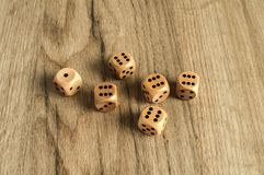 Wooden dice set on wooden board background. Wooden round corner dice six sided dots set for playing with box on wooden board surface as background Stock Image