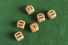 Wooden dice set on green felt cloth. Wooden round corner dice six sided dots set for playing on dark green poker table felt cloth surface as background Royalty Free Stock Photos