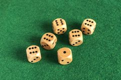 Wooden dice set on green felt cloth. Wooden round corner dice six sided dots set for playing on dark green poker table felt cloth surface as background Royalty Free Stock Photography