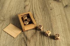 Wooden dice set on wooden board background. Wooden round corner dice six sided dots set for playing with box on wooden board surface as background Royalty Free Stock Photos