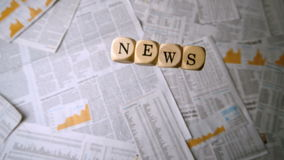 Wooden dice spelling out news falling over sheets of paper Royalty Free Stock Photos