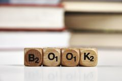 Wooden dice with the words Book with blurred books Stock Images