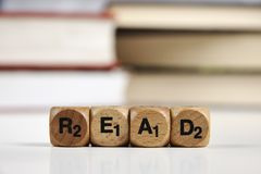 Wooden dice with the words Read with blurred books Stock Photos