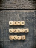 Live laugh love concept. Wooden dices with the words live laugh love on a wooden background Stock Photos