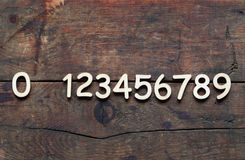 Wooden Digits Set. Set of wooden digits in a row on wood background Royalty Free Stock Photos