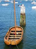 Wooden dingy moored in Plymouth Harbor Massachusetts. Wooden dingy moored in Plymouth Harbor next to the Mayflower 2 replica ship. Log piling and blue ocean in Royalty Free Stock Image