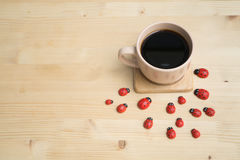 Wooden dining table with black coffee and red ladybug . Royalty Free Stock Image