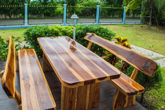 A wooden dining table set in lush garden setting stock images