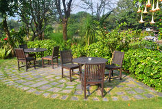 Wooden dining tables set in garden setting Royalty Free Stock Images