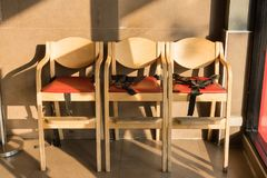 Wooden dinning chair for kids with seat belts. royalty free stock image