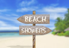 Wooden direction sign beach or showers Stock Photos