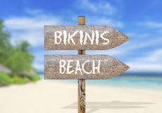 Wooden direction sign with bikinis beach Stock Photo
