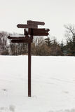 Wooden direction sign covered with snow Stock Image
