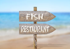 Wooden direction sign with fish restaurant. Close Royalty Free Stock Image