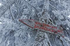 Wooden direction sign. Wooden hiking direction sign on frozen snowy fir tree trunk showing the way to Postavaru chalet in Postavaru mountain during winter stock images