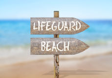 Wooden direction sign with lifeguard beach Royalty Free Stock Image