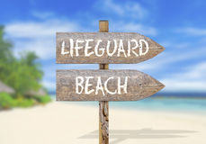 Wooden direction sign with lifeguard beach Stock Image
