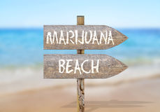 Wooden direction sign with marijuana beach Royalty Free Stock Photography