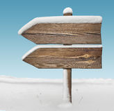 Wooden direction sign with less snow and sky bg. two_arrows-one_ Stock Image