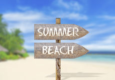 Wooden direction sign with summer beach Royalty Free Stock Images