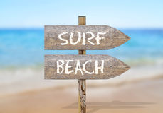 Wooden direction sign with surf beach Stock Photos