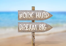 Wooden direction sign with work hard dream big. Close stock photo