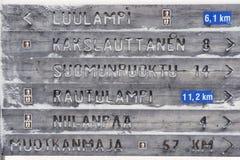 Wooden directions sign in winter in Finnish Lapland, Saariselka, Finland.  Stock Photos