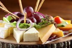 Wooden dish with cheese and fruits Royalty Free Stock Image