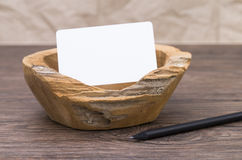 Wooden dish on old table. Image shows an old wooden dish with blank label on an wooden vintage table royalty free stock image