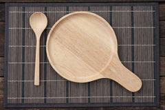 Wooden dish and spoon. Close up wooden dish and spoon on wooden table top view Royalty Free Stock Photography