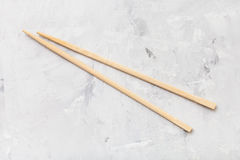 Wooden disposable chopsticks on concrete board Stock Images