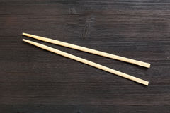 Wooden disposable chopsticks on dark brown table Stock Photography