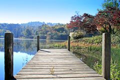 Wooden Dock in the Autumn. Wooden dock in Autumn with mountains in distantance Stock Image