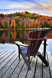 Wooden dock on autumn lake. Wooden dock with chair on calm fall lake Stock Image