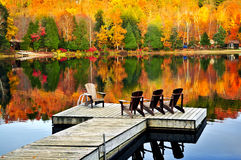 Wooden dock on autumn lake. Wooden dock with chairs on calm fall lake