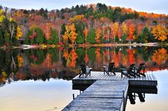 Wooden dock on autumn lake. Wooden dock with chairs on calm fall lake Stock Photo