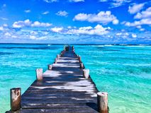 Wooden dock in blue waters royalty free stock photos