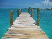 Wooden dock extending into the Caribbean Sea in the Bahamas. A wooden dock extends into the turquoise blue Caribbean Sea on an island in the Exumas region of the Royalty Free Stock Image