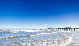 The wooden dock facing the waves. Photo taken during a trip in 2016. This wooden dock is on the beach near Daytona Beach, Florida Stock Image