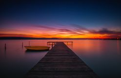 Wooden Dock and fishing boat at the lake, sunset shot. Wooden Dock and fishing boat at the lake, city lights at sunset stock images