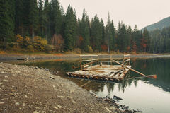Wooden dock on the lake in the autumn forest. In the mountains Stock Image