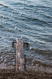 Wooden Dock in Lake Baikal. A wet wooden dock jutting into the gray waters of Lake Baikal in Siberia from a pebble beach. The water is choppy and the small waves Royalty Free Stock Images