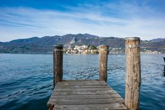 Wooden dock on Lake Orta, opposite the island of San Giulio isla. Nd with a monastery of Benedictine nuns, calm and blue lake in spring royalty free stock images