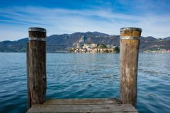 Wooden dock on Lake Orta, opposite the island of San Giulio island with a Benedictine nunnery monastery. Wooden dock on Lake Orta, opposite the island of San royalty free stock photography